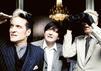 Die Band Die Ärzte: Bela B., Rod Gonzalez und Farin Urlaub in Anzügen vor einem Kronleuchter