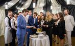 umringt von Hochzeitsgästen schneiden Tobias (Max Beier, l.) und Boris (Florian Frowein, r.) die Hochzeitstorte an, verziert mit einem Herz in Regenbogenfarben.