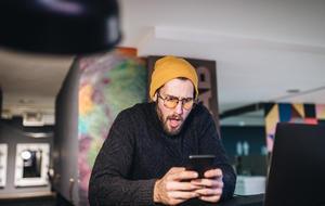 Überraschter junger Mann entdeckt Amazon Deals auf seinem Smartphone