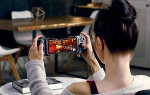 Eine rau nutzt den Handy-Controller Razer Kishi, bei dem ein Smartphone zischen zwei Controller-Hälften eingespannt wird, sodass es sich wie eine Nintendo Switch bedienen lässt.