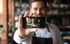 Mann hält kleines Smartphone für Selfie lächelnd vor sich