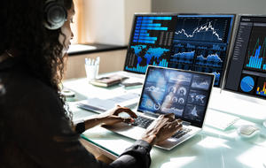 Frau arbeitet an Laptop und hat zwei externe Bildschirme angeschlossen. Alle Displays zeigen Statistiken an.