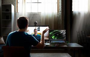 Razer Kiyo Pro Webcam auf einem Bildschirm montiert. Davor sitzt ein Mann und spricht mit einer Person auf dem Bildschirm per Videochat.