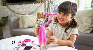 Ein Mädchen spielt mit ihrem Barbie Adventskalender