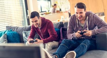 Zwei Männer spielen mit einer Konsole
