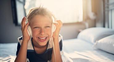 Junge liegt auf einem Bett und hört Musik über Kinderkopfhörer