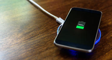 Ein Handy lädt auf einem Nachttisch auf einem Wireless Charger