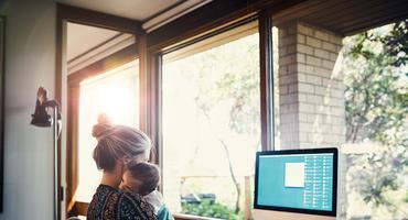 Junge Frau mit Baby im Arm sitzt vor einem Computer.