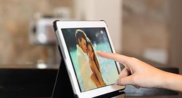 Digitaler Bilderrahmen wird von Finger einer Frau angefasst