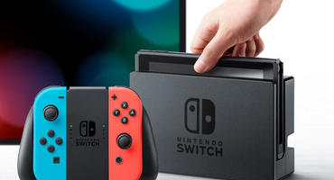 Eine Nintendo Switch wird von einer Hand aus dem TV-Dock gehoben. Im Vordergrund sind Joy-Con-Controller zu sehen, im Hintergrund ein Fernseher.