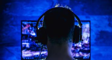 Hinterkopf eines Mannes, der ein Headset trägt und im dunklen Raum am Fernseher spielt.