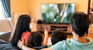 Eine Familie schaut eine Serie auf einem LCD-Fernseher.