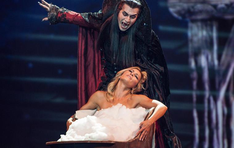 """""""Die Helene Fischer Show"""": Drew Sarich als Graf von Krolock aus dem Tanz der Vampiere und Helene Fischer auf der Bühne. Helene Fischer sitzt in einer Badewanne mit Schaum, Graf von Krolock nähert sich ihr von hinten."""