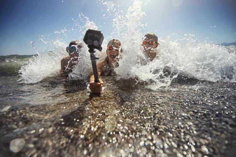 Kinder spielen in Meereswellen und filmen sich mit wasserdichter Action-Kamera.