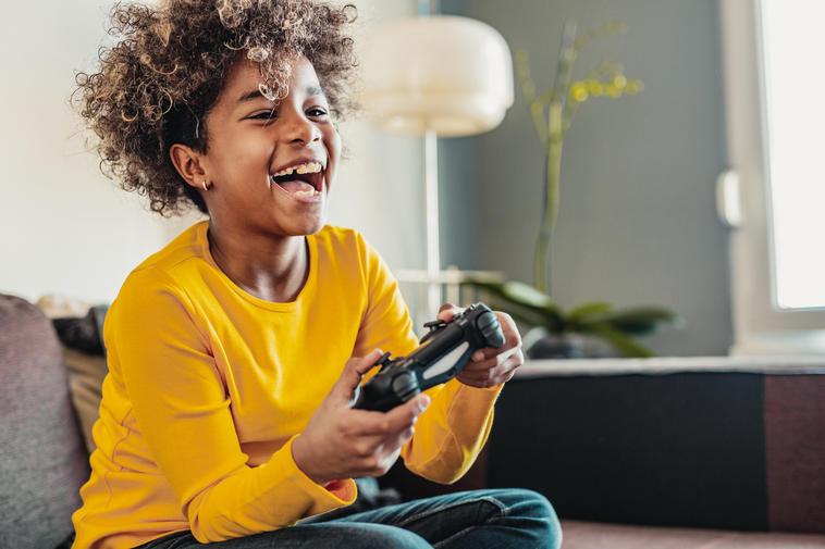 Junges Mädchen spielt mit Spielekonsole