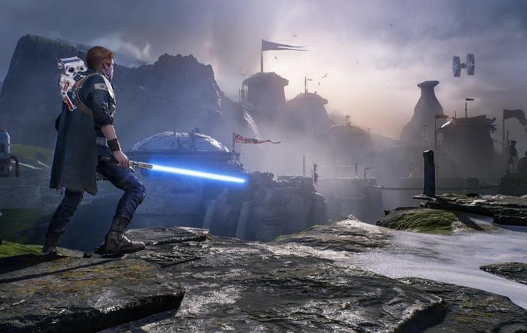 Szene aus Star Wars Jedi Fallen Order. Cal Kestis steht mit blauem Lichtschwert vor einer Basis des Imperiums