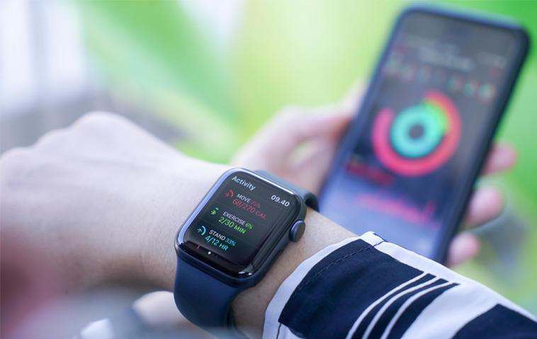 Apple Watch am Handgelenk und Handy im Hintergrund