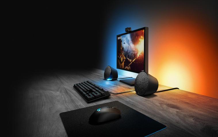 Gaming-Lautsprecher Logitech G506 auf einem Schreibtisch mit Monitor und stimmungsvollem Licht.